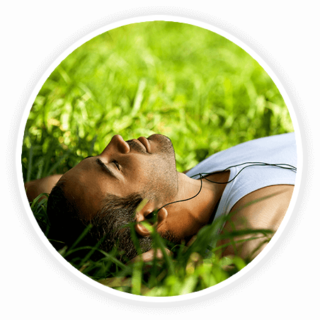 man laying in grass listening to music
