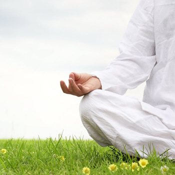 person meditating while sitting on grass